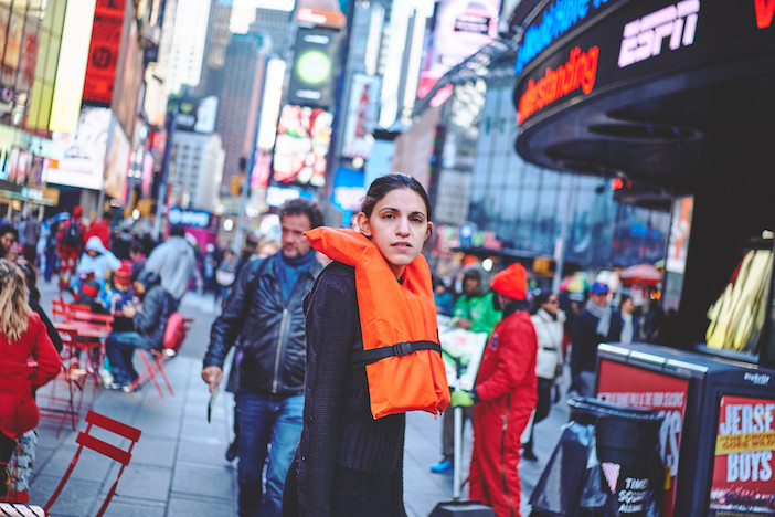 Georgia Lale wearing an orange life vest in the streets of New York for her #OrangeVest campaign